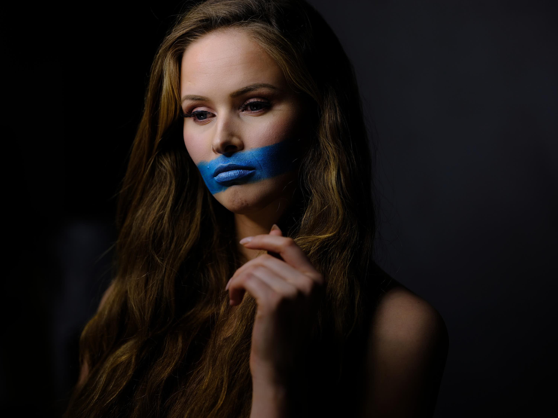 Frau mit blauer Farbe am Mund