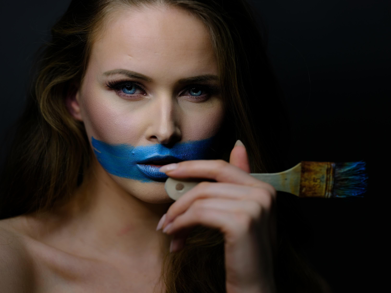 Frau mit blauer Farbe am Mund und Pinsel