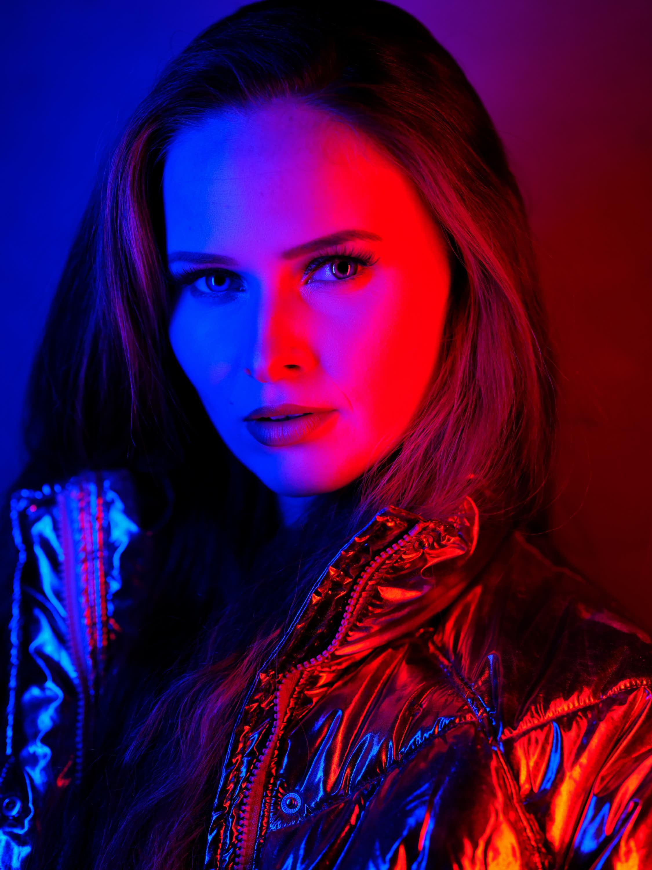 junge Frau in rotem und blauem Blitzlicht